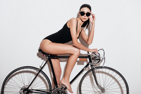 side pose: Side view of beautiful young woman in black swimsuit adjusting her sunglasses while sitting on the bicycle against white background Stock Photo