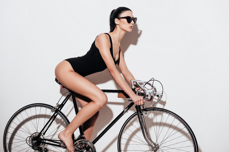 beautiful body: Side view of beautiful young woman in black swimsuit sitting on the bicycle against white background