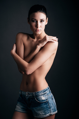 black breast: Beautiful young shirtless woman posing and looking at camera while standing against black background