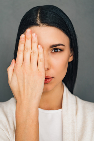 woman eye: Portrait of beautiful young woman looking at camera and covering her eye with her hand while standing against grey background