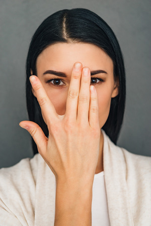 Portrait of beautiful young woman looking at camera through her fingers while standing against grey background