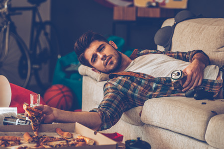 after party: Young handsome man holding pizza slice and beer can while lying on sofa in messy room after party