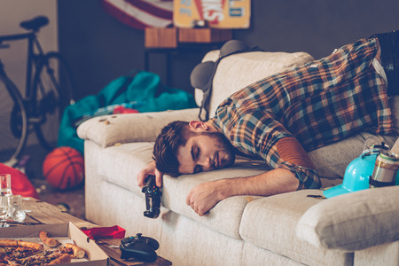passed: Young handsome man passed out on sofa with joystick in his hand in messy room after party Stock Photo
