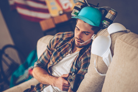 after party: Young handsome man in beer hat napping on sofa in messy room after party