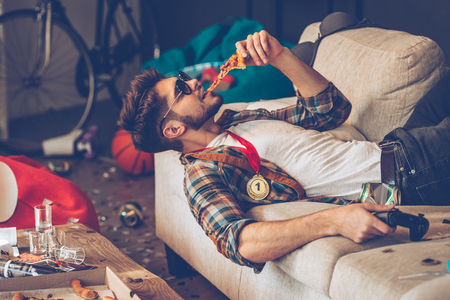 home party: Young handsome man in sunglasses eating pizza and holding joystick in his hand while lying on sofa in messy room after party