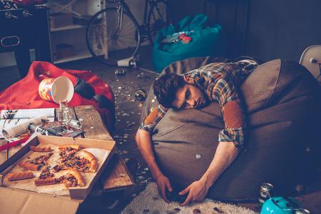 El hombre hermoso joven se desmayó en bolso de haba con joystick en la mano en la habitación desordenada después de la fiesta