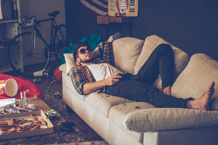 messy room: Young handsome man in sunglasses lying down on sofa with joystick in his hand in messy room after party