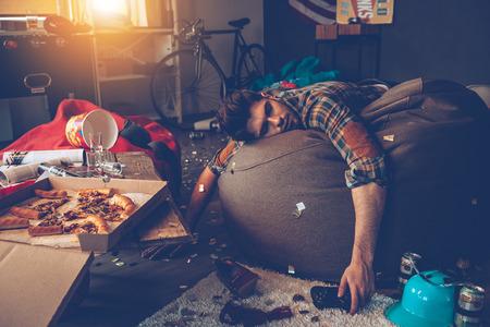 Homem considerável novo desmaiou no saco de feijão com joystick na mão no quarto bagunçado depois da festa
