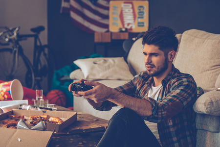 after the party: Frustrated young man holding joystick while sitting on the floor in messy room after party Stock Photo