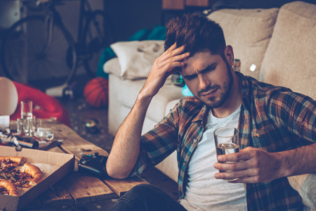 after the party: Handsome young man holding glass of water and looking exhausted while sitting on the floor in messy room after party Stock Photo