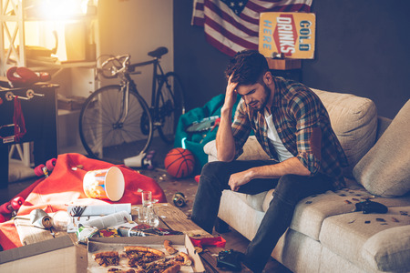 Frustrated young man keeping hand in hair while sitting on sofa in messy room after party