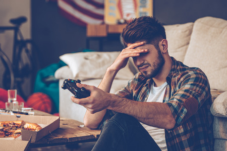 keeping room: Frustrated young man holding joystick and keeping his hand on forehead while sitting on the floor in messy room after party Stock Photo