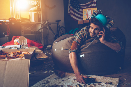 after party: Handsome young man talking on mobile phone and holding joystick while lying on bean bag in messy room after party