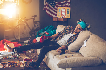 after the party: Young handsome man in boxing glove and beer hat napping on sofa in messy room after party