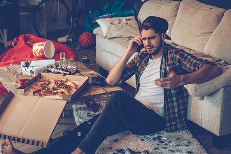 Gut aussehender junger Mann, der auf Handy spricht und gestikuliert, während in unordentlichen Zimmer nach der Party auf dem Boden sitzen