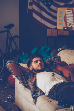 man lying down: Young handsome man lying down on sofa and napping in messy room after party