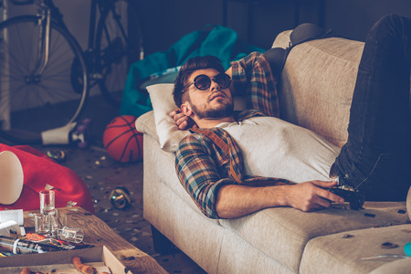 after party: Young handsome man in sunglasses lying down on sofa with joystick in his hand in messy room after party