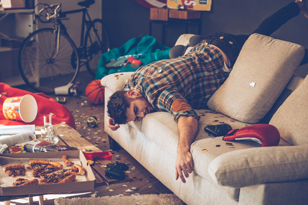 pizza box: El hombre hermoso joven se desmayó en el sofá en la habitación desordenada después de la fiesta