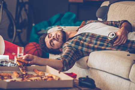 passed out: Young handsome man passed out on sofa with pizza slice and beer can in his hand in messy room after party