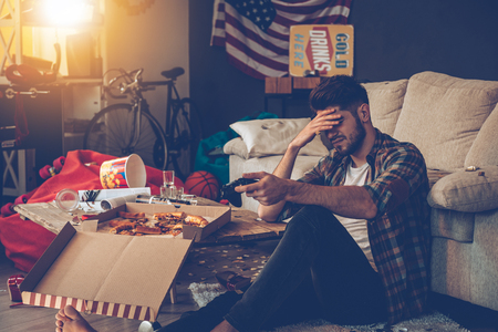 after the party: Frustrated young man holding joystick and keeping his hand on forehead while sitting on the floor in messy room after party Stock Photo