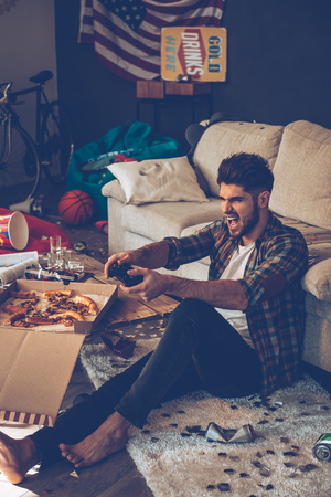 messy room: Excited young man holding joystick and keeping mouth open while sitting on the floor in messy room after party Stock Photo