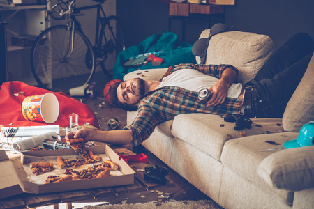 Young handsome man passed out on sofa with pizza slice and beer can in his hand in messy room after party