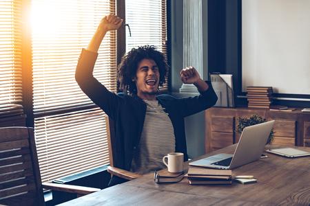 África hombre excitado joven haciendo un gesto y mantener la boca abierta mientras se está sentado en su lugar de trabajo
