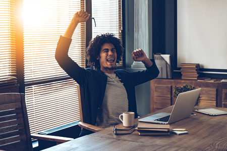 Excited junger afrikanischer Mann Gestik und Mund offen zu halten, während an seinem Arbeitsplatz sitzt