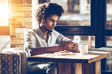 Young African man using his smartphone while sitting in cafe in front of window