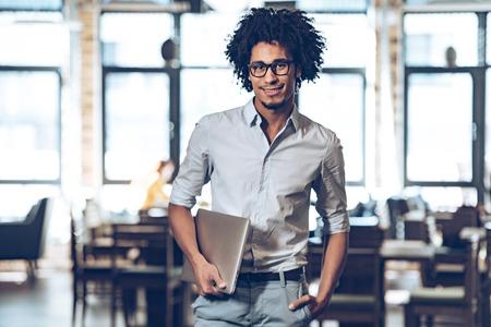 Jonge vrolijke Afrikaanse man die laptop draagt en camera kijkt met glimlach terwijl hij op cafe staat