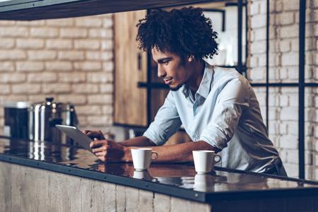 Vista lateral del hombre africano joven que usa su tableta digital mientras se apoya en el mostrador de bar con dos tazas de café Foto de archivo