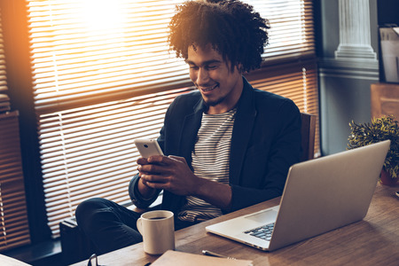 blind man: Young handsome African man using his smartphone with smile while sitting at his working place Stock Photo
