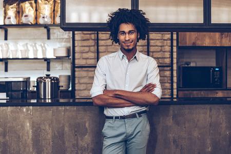 Jeune homme joyeux africain en gardant les bras croisés et regardant la caméra avec le sourire tout en se tenant au comptoir de bar Banque d'images - 54361088