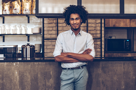 Young cheerful African man keeping arms crossed and looking at camera with smile while standing at bar counter
