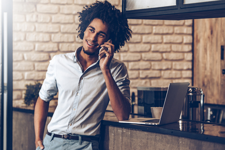 mobile business: Cheerful young African man talking on mobile phone with smile and looking away while standing at bar counter