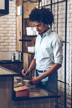 side bar: Side view of young African man stirring coffee while standing at bar counter Stock Photo
