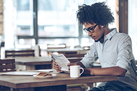 blank newspaper: Side view of young African man in glasses reading newspaper while sitting in cafe