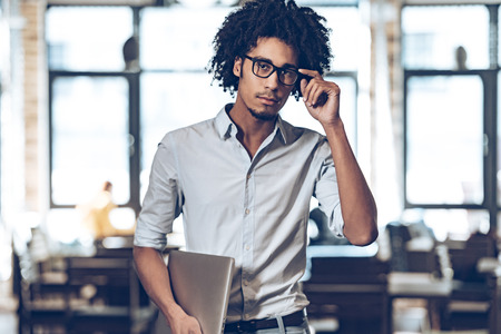 african man: Young African man adjusting his glasses and looking at camera while standing at cafe