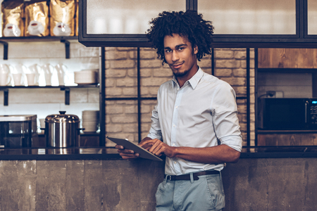 Young cheerful African man using digital tablet and looking at camera with smile while standing at bar counter Stock Photo