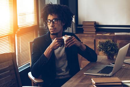 personas pensando: África hombre hermoso joven en los vidrios que sostienen la taza de café y mirando a otro lado mientras se está sentado en su lugar de trabajo