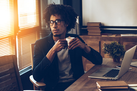 african business man: Young handsome African man in glasses holding coffee cup and looking away while sitting at his working place