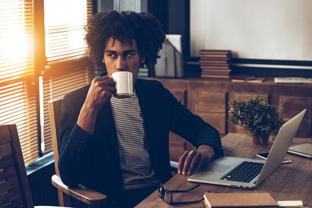 hombre tomando cafe: Joven y guapo café de consumición del hombre africano y mirando a otro lado mientras se está sentado en su lugar de trabajo
