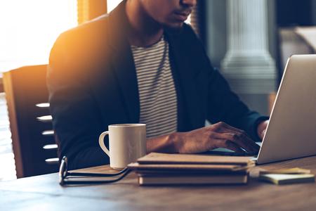 Close-up parte do homem Africano jovem usando laptop, sentado no seu local de trabalho Banco de Imagens