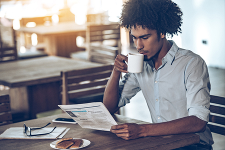 adults: Young African man reading newspaper and drinking coffee while sitting in cafe