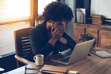 El hombre africano joven que parece agotado y cubriéndose la cara con las manos mientras está sentado en su lugar de trabajo