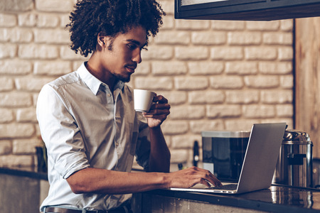 side bar: Side view of young African man using laptop and holding coffee cup while standing at bar counter