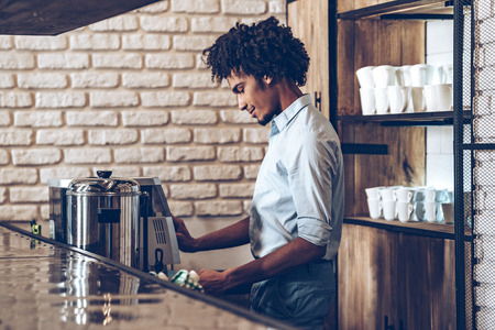 side bar: Side view of young African man using coffee machine with smile while standing at bar counter