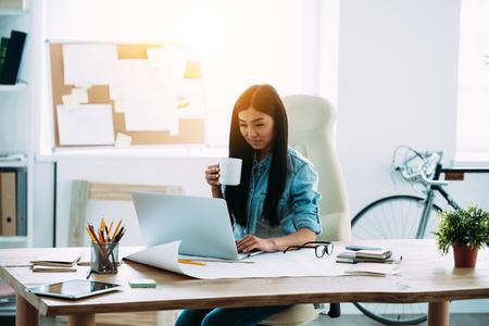 Güzel genç Asyalı kadın çalışma yerinde otururken dizüstü bilgisayar kullanıyorsanız ve kahve fincanı tutarak
