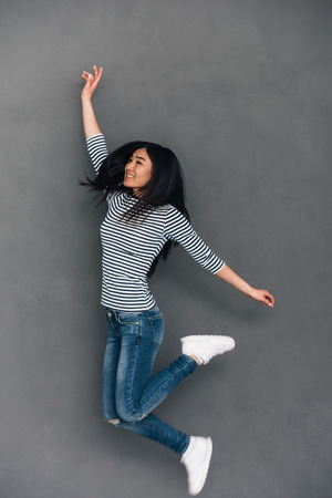 japanese ethnicity: Beautiful young cheerful Asian woman looking away with smile while jumping against grey background