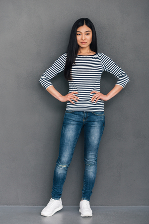 japanese ethnicity: Full length of beautiful young Asian woman keeping hands on hips and looking at camera while standing against grey background